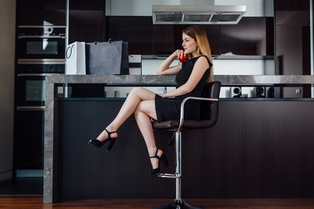 Full-length portrait of elegant woman with fair hair wearing black dress and high heels sitting on a bar chair in kitchen
