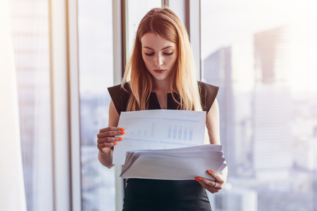 Confident female director holding documents standing in modern office against panoramic window
