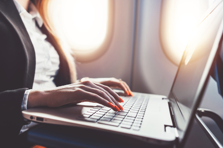 Close-up of female hands using laptop. Woman working while going on business trip by plane