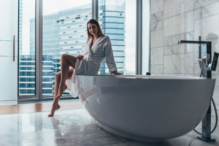 Back view of young woman wearing white bathrobe standing in bathroom looking out the window with bathtub in foreground 版權商用圖片 - 116782392