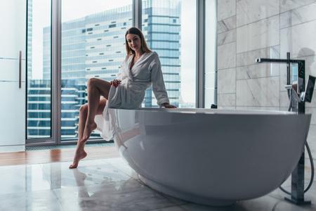 Punto di vista posteriore dell'accappatoio bianco d'uso della giovane donna che sta nel bagno che guarda fuori dalla finestra con la vasca in priorità alta Archivio Fotografico