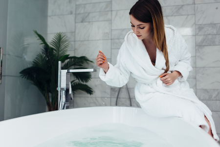 Pretty slim woman wearing bathrobe sitting on edge of bathtub filling up with water