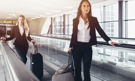 Two confident women wearing formal suits standing on moving walkway in airport