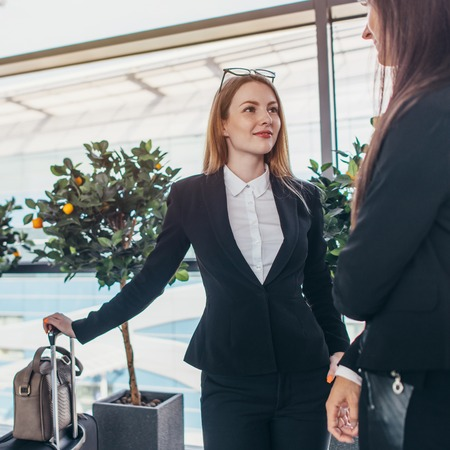 Two smiling business partners talking standing in airport