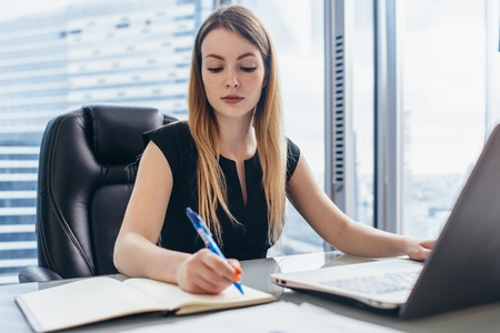 Concentrated businesswoman working writing notes in notebook sitting at desk in office Imagens