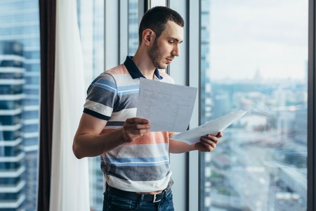 Businessman holding reading documents standing by the window in office Imagens