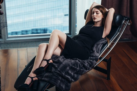 Portrait of female model wearing short black dress and high heels relaxing on chair Banco de Imagens