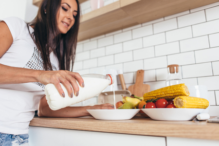 Woman having breakfast pouring milk into a bowl with muesli in kitchen