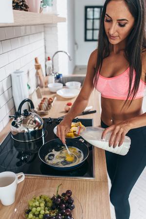 Woman making omlette breakfast. Pour milk into frying pan with eggs Foto de archivo - 116782628
