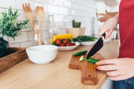 Vrouw snijden komkommer op het houten bord. Stockfoto