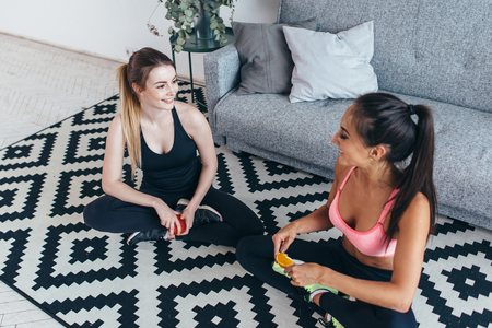 Smiling fit women wearing sportswear sitting on floor eating fruits and talking