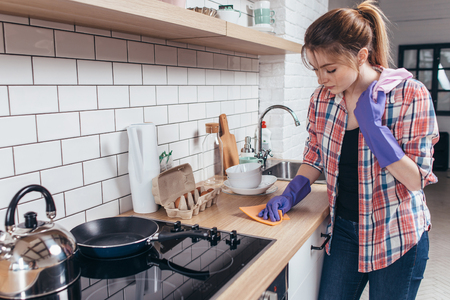 Young woman wiping table in the kitchen.