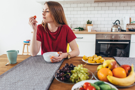 Woman at home eating fruits and vegetables top view. Imagens