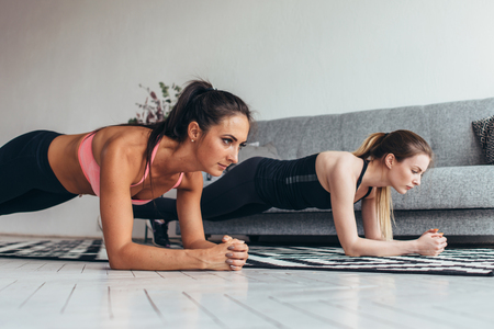 Two fit women doing plank exercise on floor at home Training back and press muscles, sport, fitness workout