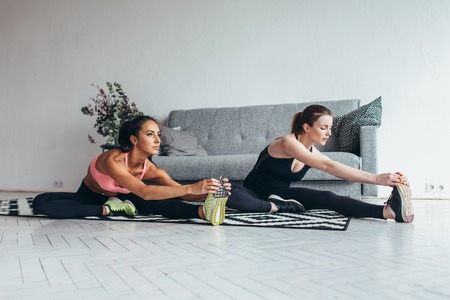 Fit women doing stretching while sitting on the floor at home Imagens