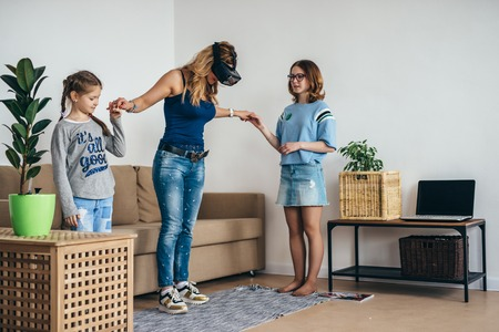 Woman using VR headset glasses virtual reality at home standing on living room with kids. Stock Photo