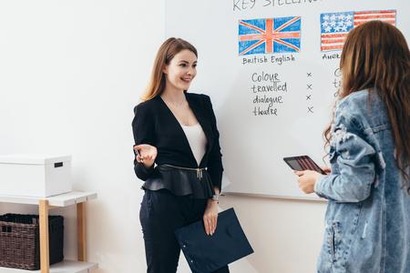 Mujer joven enseñando inglés a estudiantes adultos en la escuela de idiomas