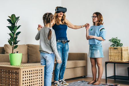 Woman using VR headset glasses virtual reality at home standing on living room with kids. Imagens