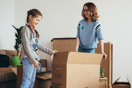 Family with cardboard boxes in new house at moving day