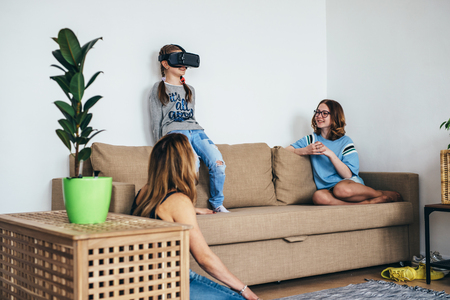 Little child girl playing game in virtual reality glasses