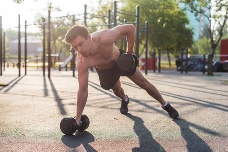 Muscular man lifts the dumbbell. Back exercise. Single arm dumbbell row.