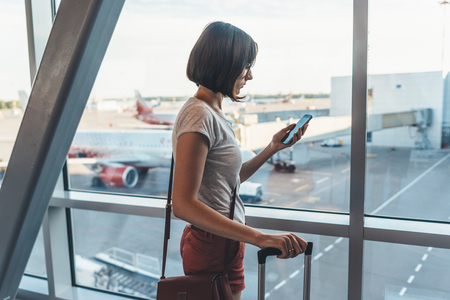 Young casual female traveler in airport, holding smart phone near gate windows at planes on runway. Stock Photo