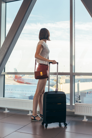 Young casual female traveler in airport near gate windows at planes on runway.