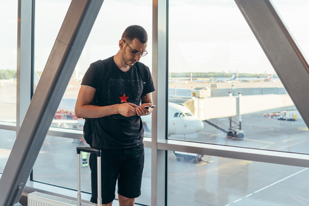 Young casual male traveler in airport, holding smart phone near gate windows at planes on runway. Stock Photo - 124622549