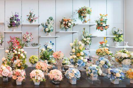 Ramos decorativos de flores de colores en el escaparate de la tienda Foto de archivo