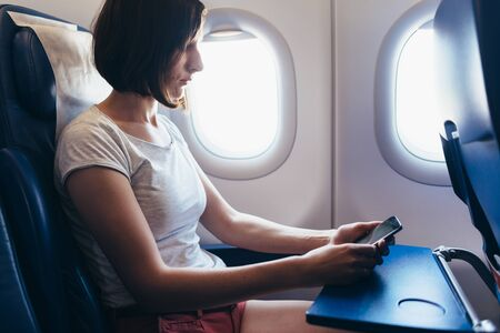 Woman traveling by plane. Girl with a phone in her hands sitting on the airplane.