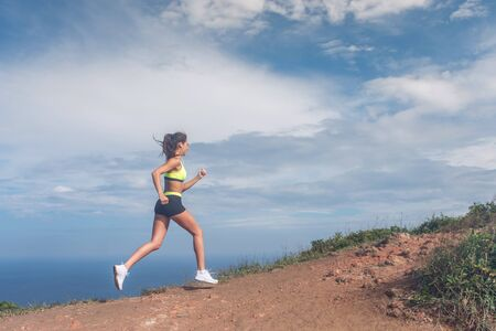 Athletic woman running up the mountain with sky and sea in background. Professional runner doing cardio work-out outdoor in natural landscape