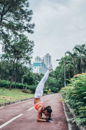 Sportswoman doing handstand yoga exercise standing on her forearms with straight legs path in the park view of city buildings Foto de archivo
