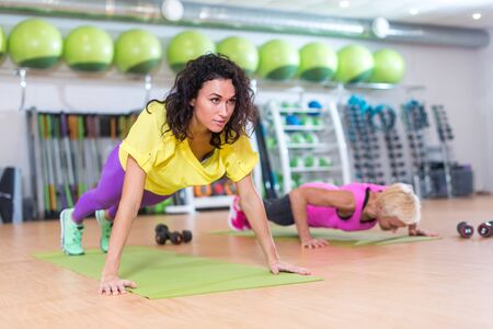 Two young women doing squat exercises standing back to with a Swiss ball between them. Female athletes working-out in gym. Stock Photo