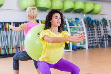 Two young women doing squat exercises standing back to with a Swiss ball between them. Female athletes working-out in gym. Stockfoto