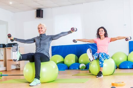Active women sitting on exercise balls lifting legs and doing dumbbell lateral raise. Two mature females working out in a gym