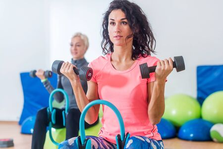 Slim sporty women training sitting on exercise balls holding dumbbells and squeezing Pilates Ring between their legs during group fitness studio class indoors