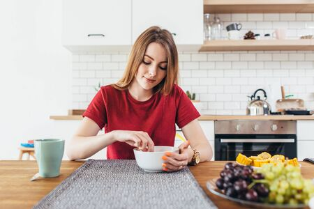 Young beautiful woman eating fruits and vegetables healthy food in kitchen. Stock Photo