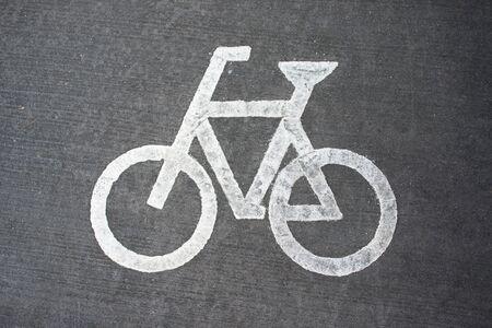 White bicycle sign on asphalt bike lane.