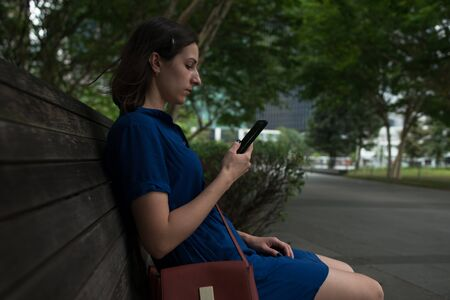 Side view of a young woman sitting on a bench in park holding her smartphone