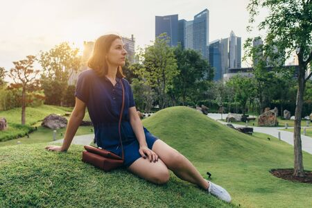 Beauty young woman sitting on the grass Portrait of girl outdoors