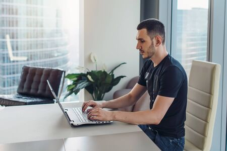 Man sitting at workplace and using laptop