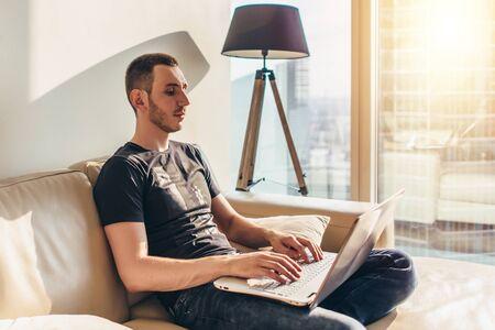 Junger Mann mit Laptop beim Sitzen auf einem Sofa