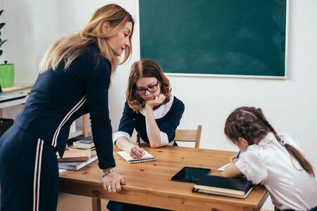 Pupils and female caucasian teacher in classroom Zdjęcie Seryjne