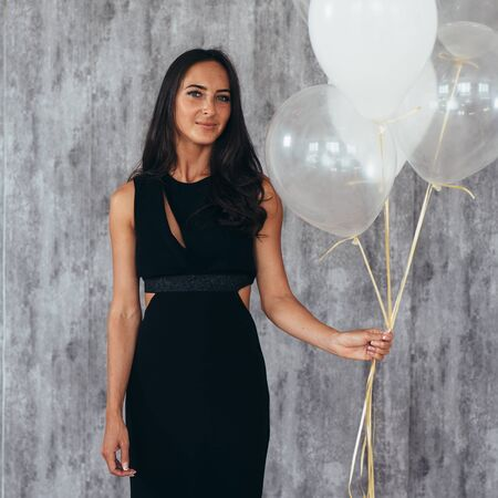 Cheerful young woman with balloons standing and smiling