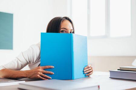 Belle étudiante se cachant derrière le livre