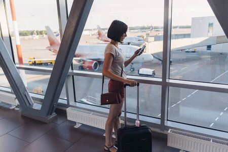 Young woman standing near window at airport holding mobile phone