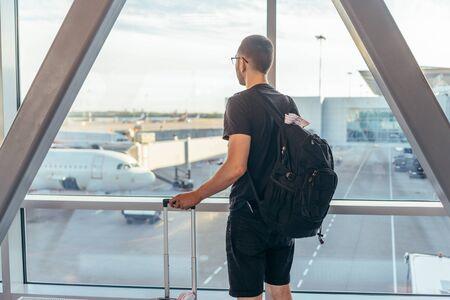 Man in airport near gate windows at planes on runway. Zdjęcie Seryjne