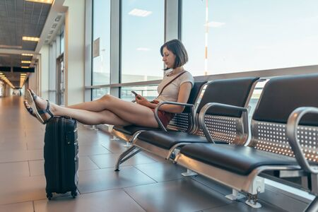 Female tourist sitting on bench with baggage in waiting room at airport.