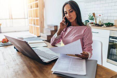 Mujer pensativa hablando por teléfono móvil, leyendo documentos Foto de archivo
