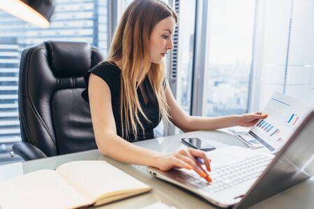 Vrouwelijke directeur die in bureauzitting bij bureau werkt dat bedrijfsstatistieken analyseert die diagrammen en grafieken houden die laptop met behulp van